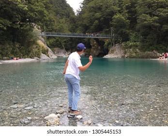 Boy skimming stones at rock pool. Blue pools, New Zealand