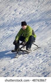 Boy Sledding Down Snowy Hill In Winter