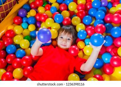 Boy sleep in a room full of balls