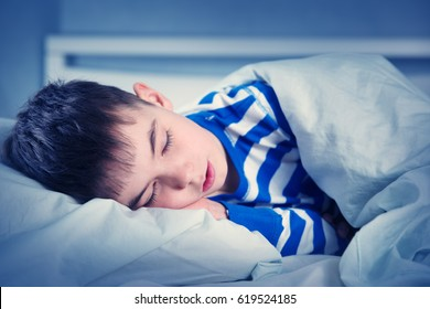 Boy sleeping in bed in pajamas. Child lying in bed on pillow at night