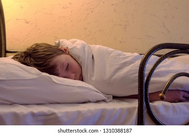 Boy is sleeping at hostel on bunk bed on top bed.