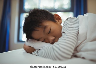 Boy sleeping on the bed in bed room at home