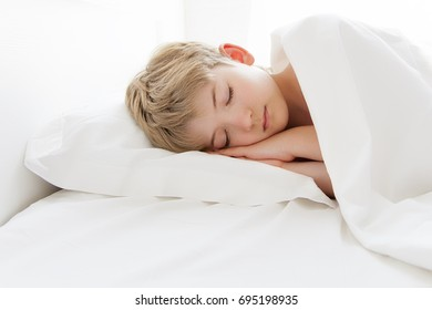 The boy is sleeping on his side in a white bed. Hands under the cheek. Early morning. Horizontal color image. Close-up