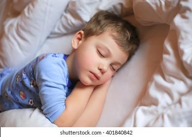 Boy sleeping in pajamas on white bed