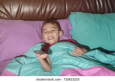 The boy sleeps on the bed and holds the TV remote and smiles happily, concepts of technology and entertainment.
