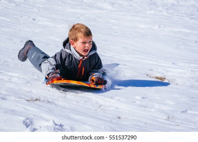 Boy sliding down a snow hill on his sled