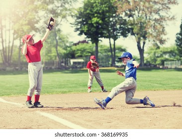 Boy sliding into base during a baseball game with Instagram style filter, focus is on catcher.