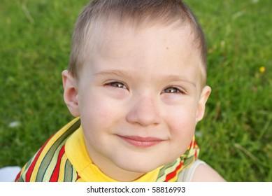The boy smiles, background green grass,portrait