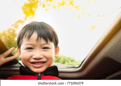 The boy smiles in the car