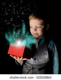 Boy smiles and holding a gift in magic packing on a black background