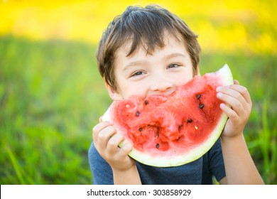 Boy smiling and eating watermelon