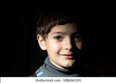 Boy with smiling face half in dark, copyspace