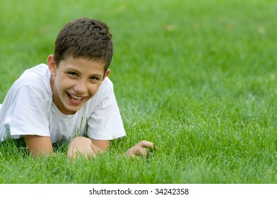 a boy is smiling on the green grass