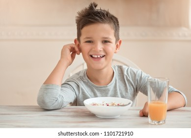boy smiling over a plate with a healthy breakfast