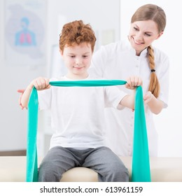 Boy and smiling physiotherapist exercising with elastic band