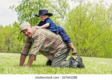 Boy smiling and riding on Grandfather's back