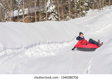 boy snow tubing in a park