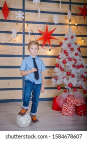 Boy soccer player in christmas time. Young soccer player in the New Year's interior. child on New Year's Eve. Waiting for a miracle from Santa Claus