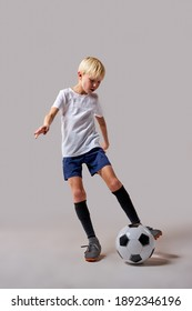 boy soccer player playing with ball, kicking it, training before match. isolated in studio, wearing uniform
