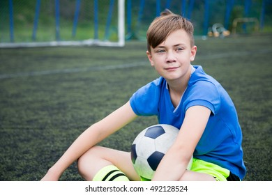 Boy soccer player sitting on football field