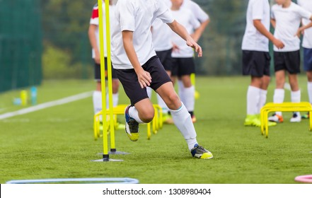 Boy Soccer Player In Training. Boy Running Between Cones During Practice in Field on Sunny Day. Young Soccer Players at Speed and Agility Practice Session