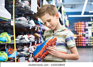 Boy with soccer shoes in the sports store
