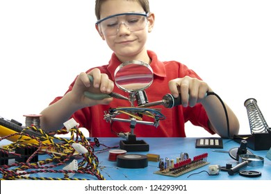 Boy soldering a component onto a printed circuit board while wearing safety glasses and red shirt.  He is surrounded with miscellaneous electrical parts.
