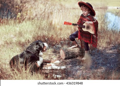 A boy in a sombrero sings and plays the guitar , and the dog hears