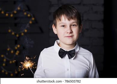 the boy with sparklers on dark background