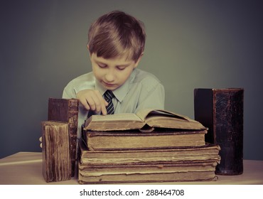 The boy spends time reading old books