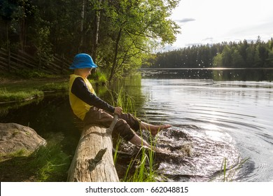 The boy splashes by  his feet in the lake, summer in Finland