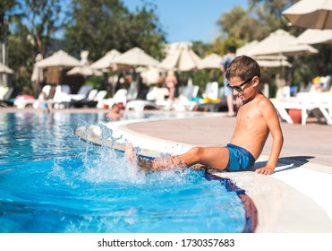 A boy splashes water in the pool.