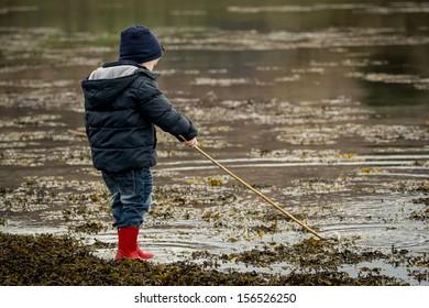 boy splashes in water with stick