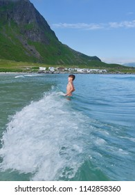 Boy splashing in a cold Norwegian sea on Lofoten islands on Ramberg beach