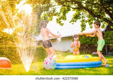 Boy splashing girls with water gun in the garden