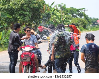 Boy are splashing water to friend on motercycle in Songkran festival in Thailand on April 13, 2018. Many boy and girl playing water at the street in their local.