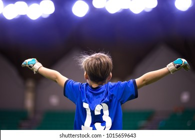 Boy sport soccer player celebrating the victory. Child winner. Cheering kid after score the goal. Football futsal indoor tournament for school kids