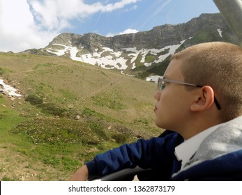 A boy in a sports jacket looks carefully at the mountains on the cable car in Sochi