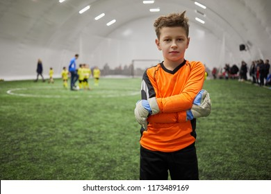 Boy in sports uniform with goalkeeper gloves on hands standing on indoor football field.