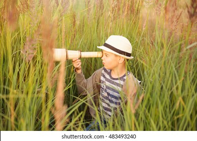 Boy spying through telescope at sunset. Concept illustration of childhood, future and travel. Natural light.