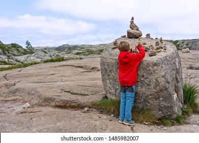 Boy stacking stouns on the hiking way to Preikestolen rock, Norway.