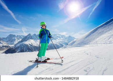 Boy stand on fresh ski slope over mountain peaks