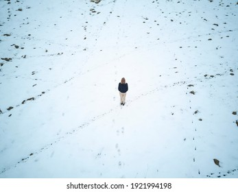 Boy standing alone in the middle of a snowy meadow. human and animal footprints in the snow. Concept of loneliness. Top view