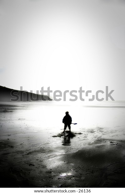 Boy standing alone on a beach with his spade.