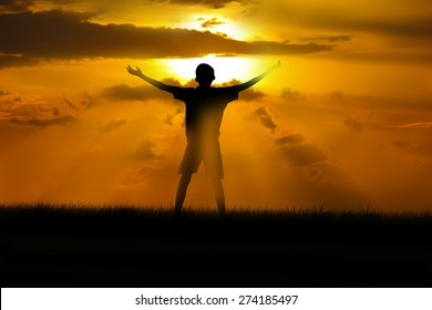 boy standing arms out stretched at sunset.