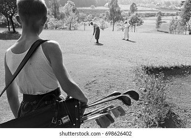 Boy standing with bag with golf clubs and watching two men playing golf