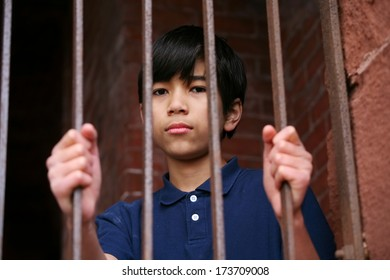 Boy standing behind bars, sad  or wary expression.