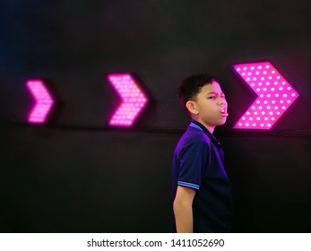 Boy Standing by Dark Wall with Illuminated Vibrant Pink Arrows
