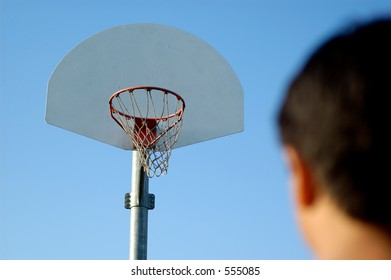 Boy standing in front of basketball hoop looking at it. Shallow DOF, focus on basketball hoop.