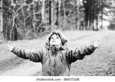 boy standing with his arms raised